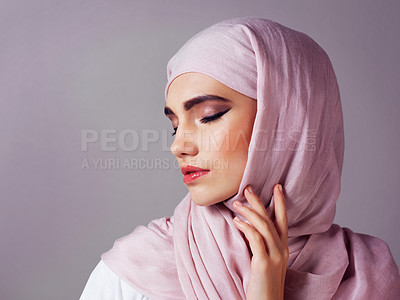 Buy stock photo Studio shot of a confident young woman wearing a colorful head scarf while posing against a grey background