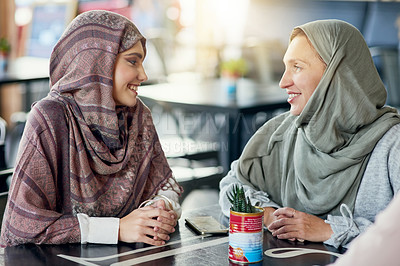 Buy stock photo Shot of a two happy women chatting in a cafe