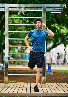 Buy stock photo Portrait of a sporty young man stretching his legs while exercising outdoors