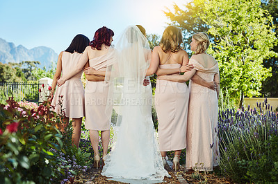 Buy stock photo Rearview shot of a young bride and her bride's maids standing together outside during the day