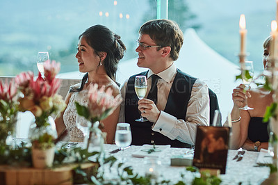Buy stock photo Shot of a cheerful young bride and groom seated at a table together while holding champagne glasses for a celebratory toast