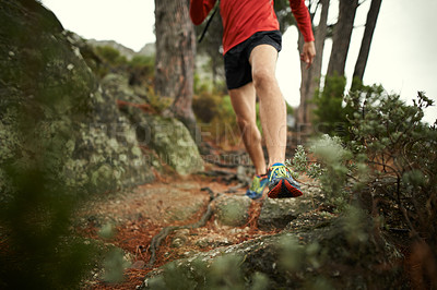 Buy stock photo Low angle shot of an unrecognizable man out running through a rough terrain