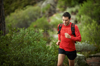 Buy stock photo Shot of a sporty young man out for a run in the mountains