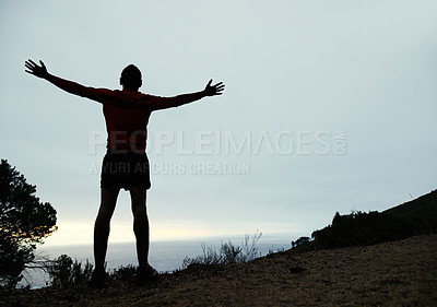 Buy stock photo Rearview shot of a young man standing with his arms outstretched