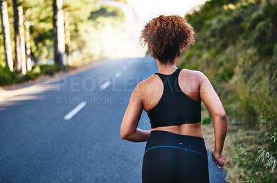 Buy stock photo Rearview shot of a young woman out for her morning run