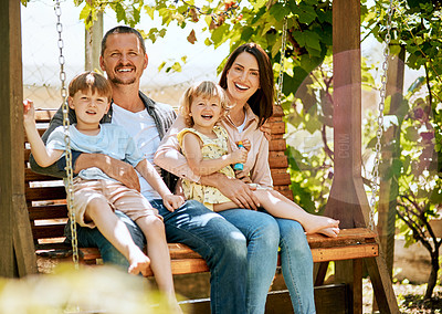 Buy stock photo Portrait of a family of four relaxing together on a garden swing