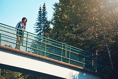 Buy stock photo Shot of an attractive young woman standing on a bridge surrounded by nature