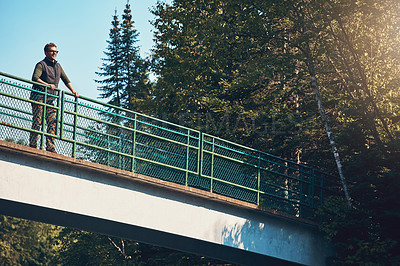 Buy stock photo Shot of a young man standing on a bridge surrounded by nature