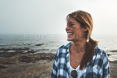 Buy stock photo Shot of a cheerful young woman standing on rocks next to the ocean while laughing outside during the day