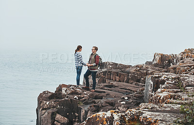 Buy stock photo Shot of a loving young couple standing hand in hand on a mountaintop