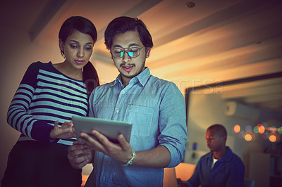 Buy stock photo Shot of two young designers working late on a digital tablet in an office
