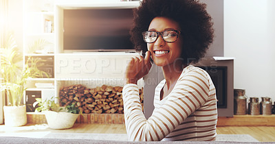 Buy stock photo Portrait of a cheerful young woman wearing glasses while being seated next to a couch with her hand touching her face at home