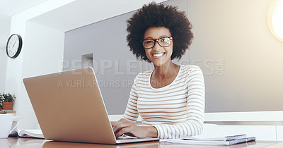 Buy stock photo Portrait of a cheerful young woman typing and working on a laptop while being seated next to a table at home