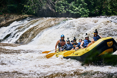 Buy stock photo Shot of a group of determined young people on a rubber boat busy paddling on strong river rapids outside during the day