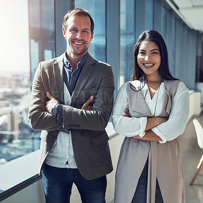 Buy stock photo Portrait of two businesspeople standing with their arms crossed in an office