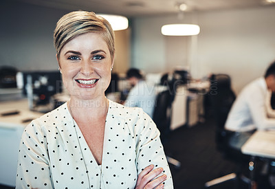 Buy stock photo Portrait of a businesswoman in the office while her colleagues are working in the background