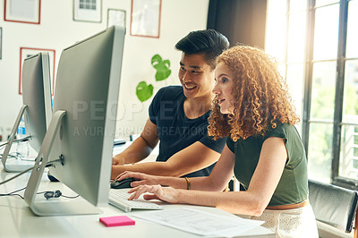 Buy stock photo Cropped shot of two young creative businesspeople working on a computer in their office