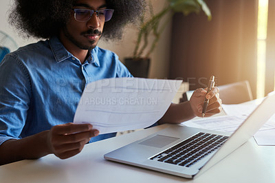 Buy stock photo Cropped shot of a handsome male designer looking at some paperwork while working in his office