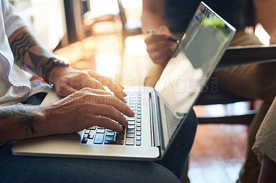 Buy stock photo Cropped shot of an unrecognizable male designer working on a laptop during a meeting in the boardroom