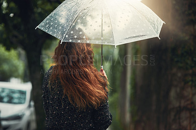 Buy stock photo Rearview shot of an unrecognizable woman walking in the rain outside