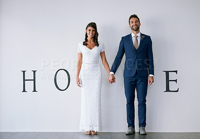 "Buy stock photo Concept studio shot of a bride and groom making an M in the word ""home"" against a wall"