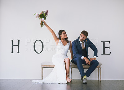 """Buy stock photo Concept studio shot of a bride and groom making an M in the word """"home"""" against a wall"""
