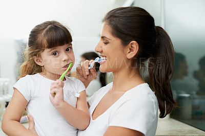 Buy stock photo Portrait of a mother and daughter brushing their teeth together in the bathroom at home