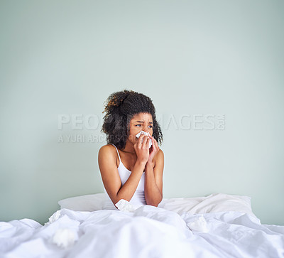 Buy stock photo Shot of a uncomfortable looking young woman holding her nose with a tissue after waking up from sleeping in her bed