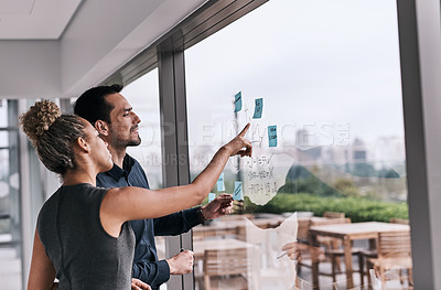 Buy stock photo Shot of two businesspeople brainstorming on a glass wall in an office