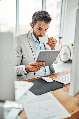 Buy stock photo Shot of a handsome young businessman drinking coffee while working on a digital tablet in an office