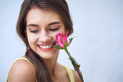 Buy stock photo Studio closeup of a cheerful young woman holding a pink rose next to her face while standing against a grey background