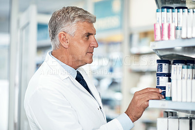 Buy stock photo Cropped shot of a mature male pharmacist checking products while working in a dispensary