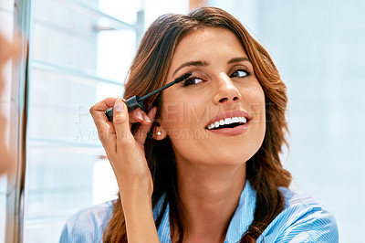 Buy stock photo Cropped shot of a beautiful young woman applying mascara to her lashes at home