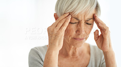 Buy stock photo Shot of a senior woman suffering from a headache at home