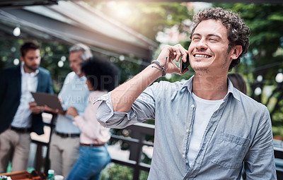 Buy stock photo Shot of a businessman talking on a cellphone outside with his colleagues in the background