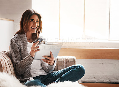 Buy stock photo Shot of an attractive young woman using a digital tablet and credit card on the sofa at home