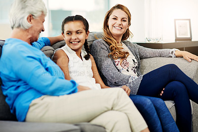 Buy stock photo Cropped shot of a senior woman sitting on the sofa at home with her daughter and granddaughter