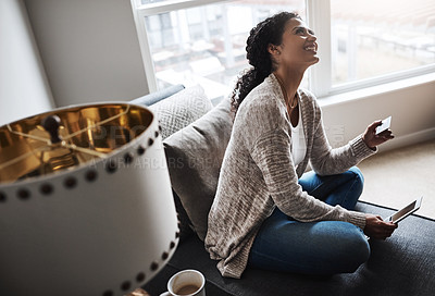 Buy stock photo Shot of a cheerful young woman relaxing on a chair while  doing online shopping on a digital tablet at home