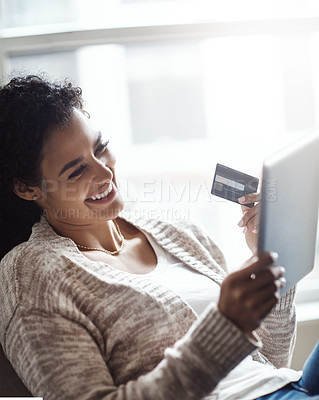 Buy stock photo Shot of an attractive young woman using a digital tablet and credit card at home