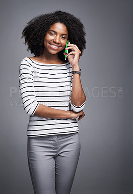 Buy stock photo Studio portrait of a young woman using a mobile phone against a gray background