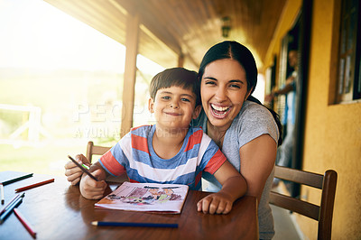 Buy stock photo Cropped shot of a young beautiful mother colouring in pictures with her adorable son at home