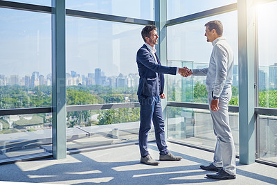 Buy stock photo Shot of two businessmen shaking hands in an office