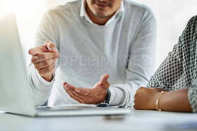 Buy stock photo Closeup shot of two unrecognizable businesspeople using a laptop together in an office