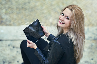 Buy stock photo High angle shot of an attractive woman using a digital tablet in the city