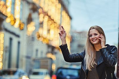 Buy stock photo Shot of an attractive woman using a mobile phone while calling a cab in the city