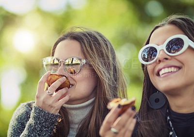 Buy stock photo Cropped shot of two attractive young women eating a peach while sitting in the park