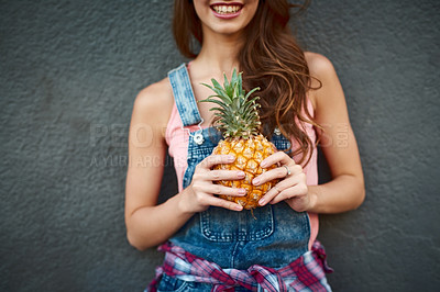 Buy stock photo Shot of an unrecognizable young woman holding a pineapple while standing against a grey background