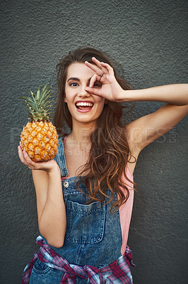Buy stock photo Portrait of a carefree young woman showing a hand gesture on her face while holding a pineapple against a grey background
