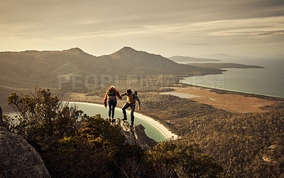 Buy stock photo Full length shot of an affectionate young couple hiking through the mountains