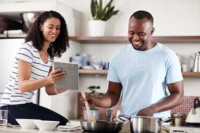 Buy stock photo Cropped shot of a young married couple using a tablet while cooking together in the kitchen at home